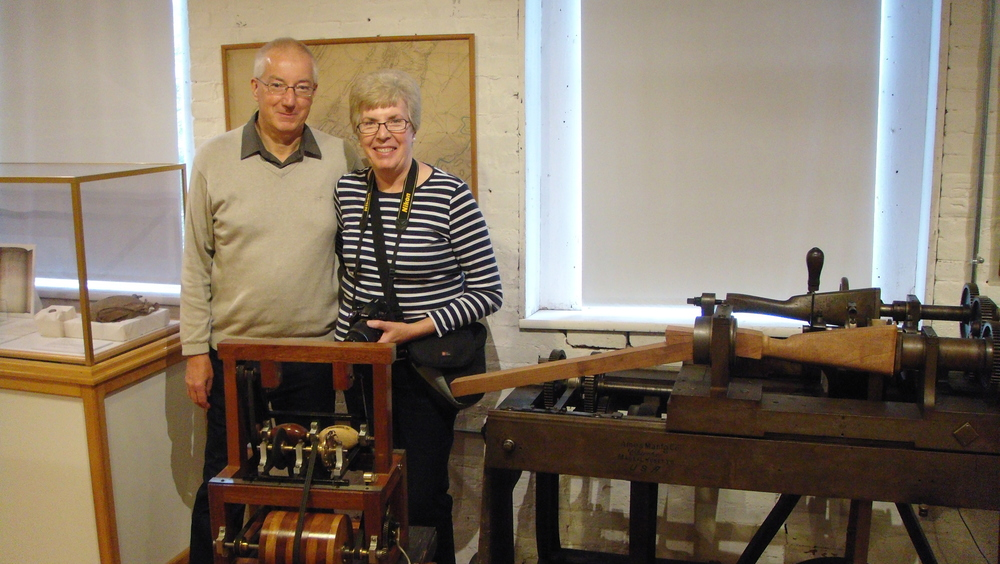Mike & Lyn Jones, standing behind a model of the Blanchard lathe of 1822, which his father built.