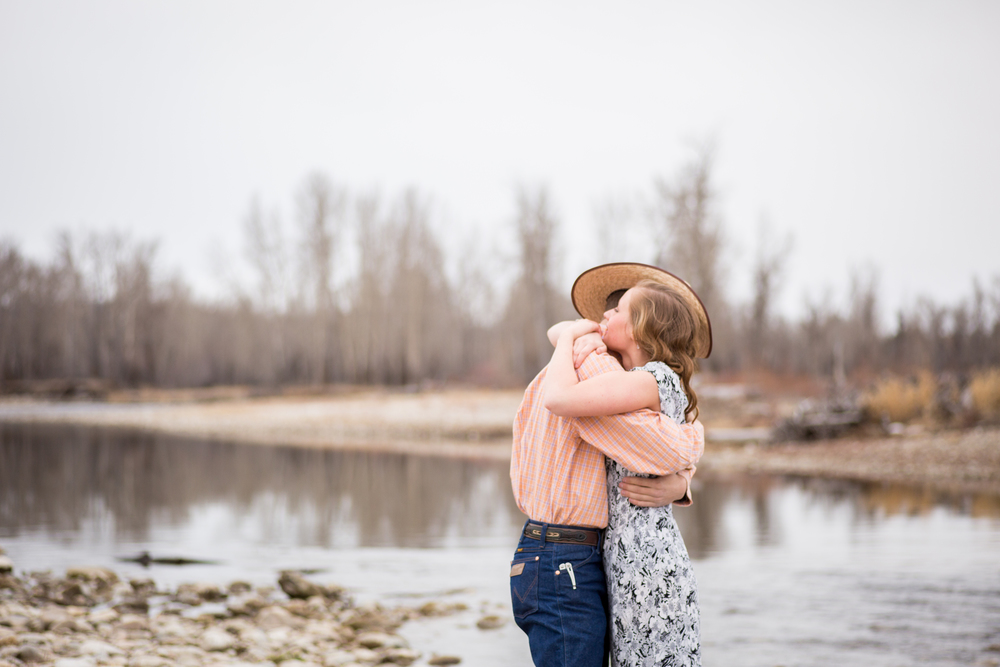 montana engagement by river couple hugging