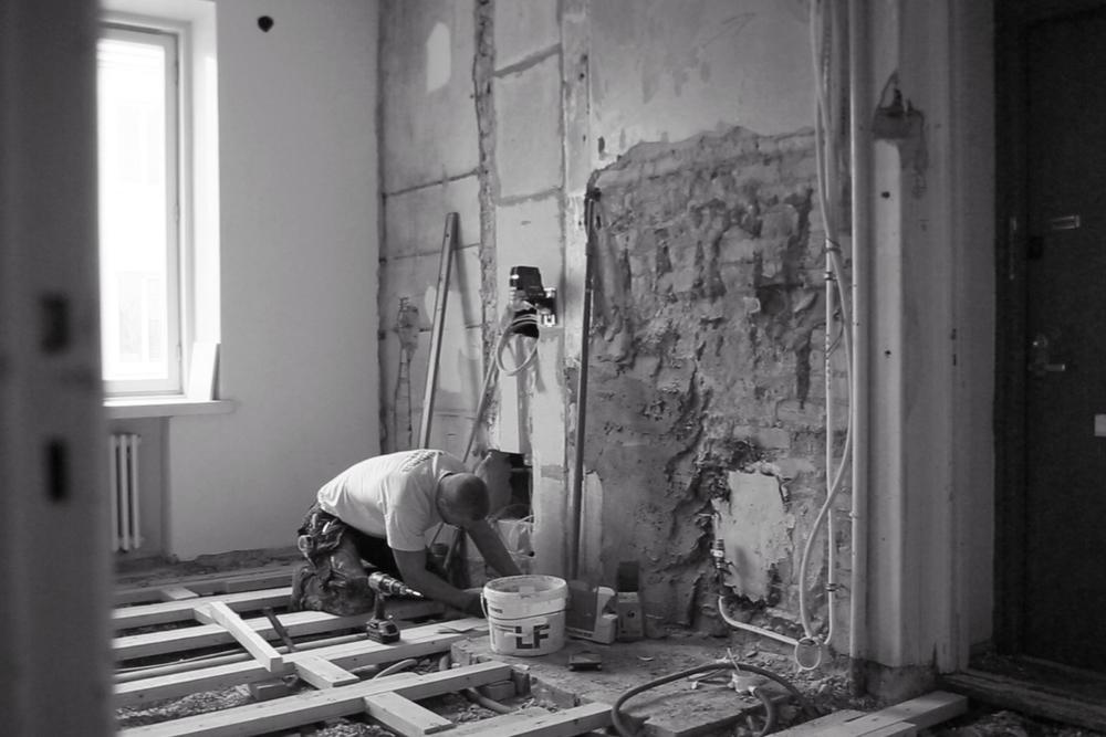 Lattiapinnat on purettu ja seinien vanhan rappauksen poiston jälkeinen täyttötyö on käynnissä. Jaanek vaa´ittaa korkoja lattiarungolle.
