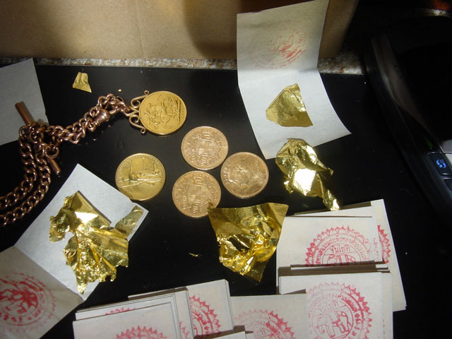 Shown: Gold coins and a pack of 100 gold leaves from Bangkok, Thailand. Each gold leaf is less than a micrometer thick (typically about 100 nm) and is so light and delicate that the smallest puff of air can blow it away. Source: Wikimedia Commons.