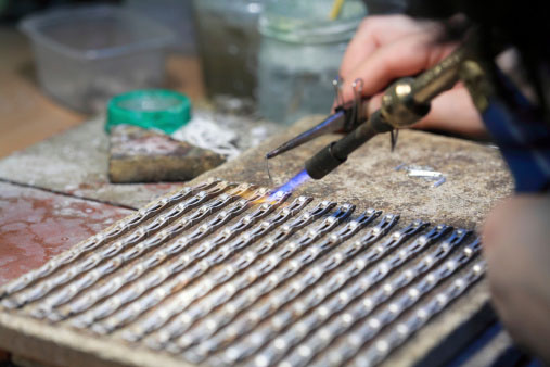 Photo of jeweler using recyclable silver solder to make silver jewelry, both of which you can recycle profitably with Specialty Metals, along with gold solder and gold jewelry.