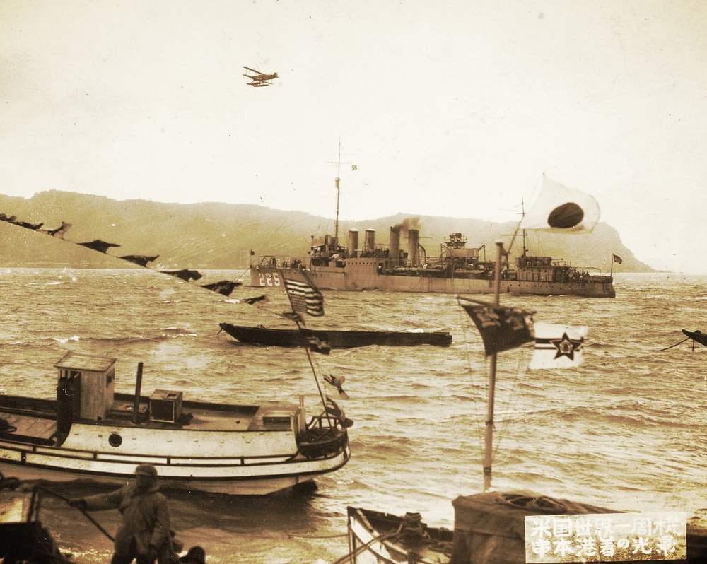 One of the Cruisers flies over the Port of Kushimoto, Japan. The large ship is the American four-funnel destroyer USS Pope (DD-225).  The Pope was on a goodwill tour to Japan in 1924 to back up the coincident arrival of the Douglas World Cruisers flight.