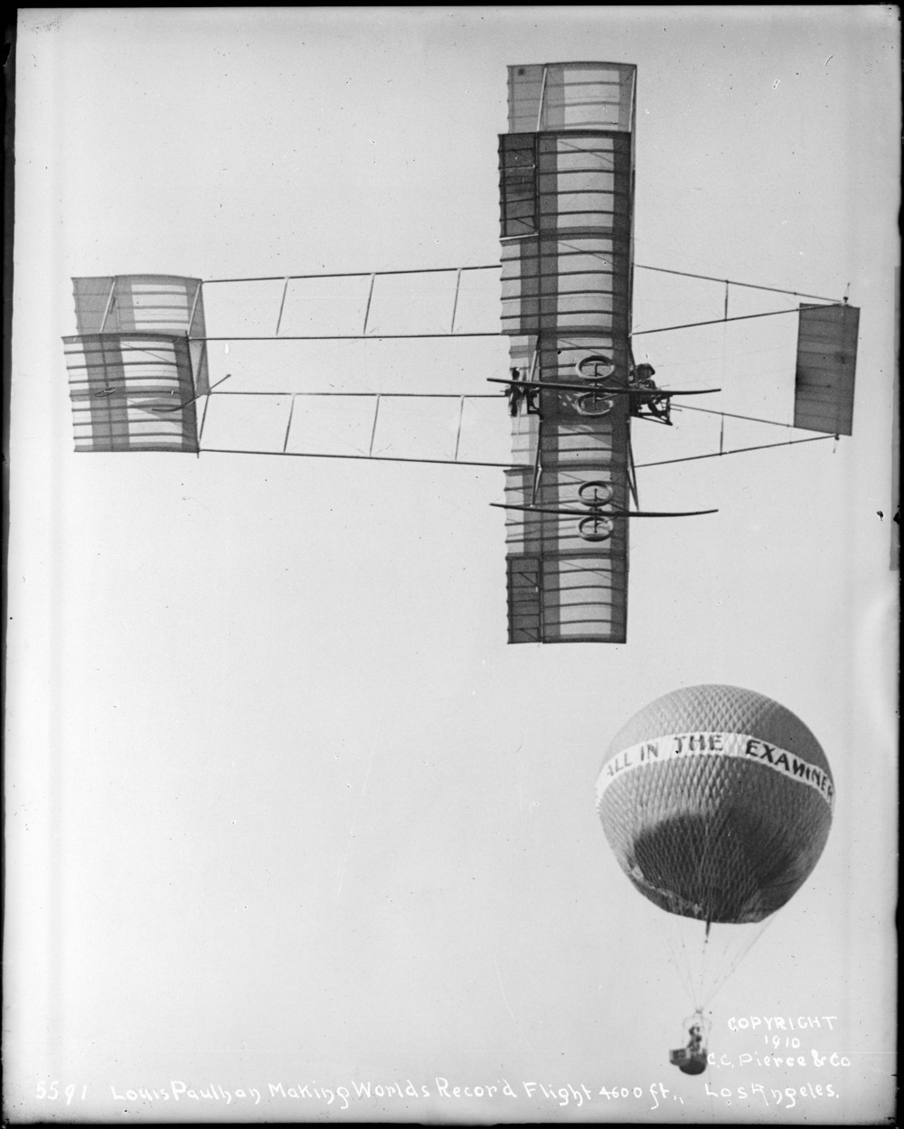 Louis Paulhan flying near a hot-air balloon in his Henry Farman biplane.  (USC Special Collection)