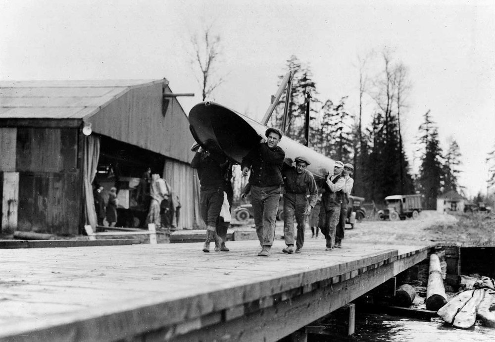 Boeing workers carrying the enormous pontoons across the dock.  (Museum of Flight)