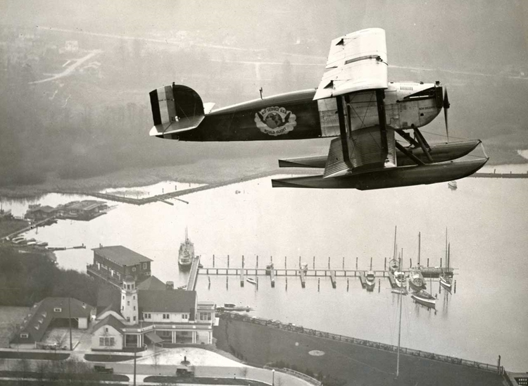 World Cruiser #4, The  New Orleans , wings it's way over the Seattle Yacht Club.  (Dempster Collection)