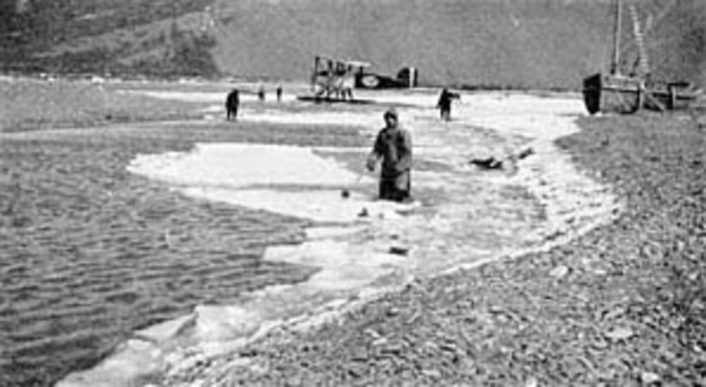 """Maj. Martin (foreground) chops ice from a creek at Kanatak, Alaska. World Cruiser """"Seattle"""" is in the background. (Photo courtesy of USAF Academy Library Special Collections)"""