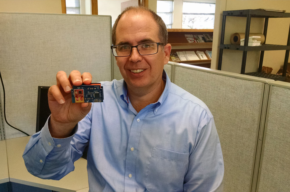 Matt simms holding one of his recently designed circuit boards utilizing Microchip modules.