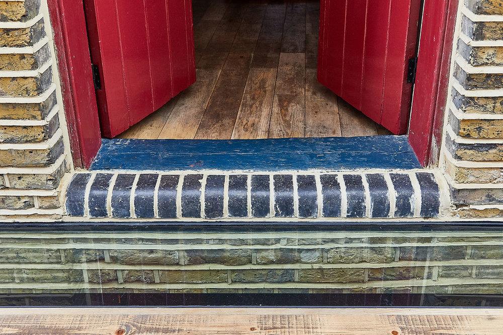 The new access shows the integration between old an new: old oak->rebuilt blue bricks->glass floor->heated oak flooring