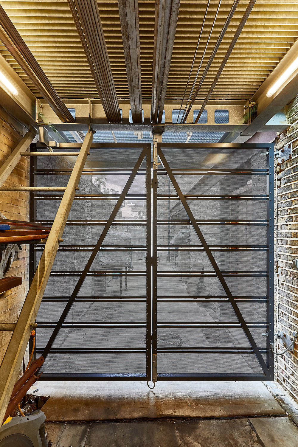The alleyway gates under the extension were designed with perforated aluminium sheets to maintain the visual permeability at both levels