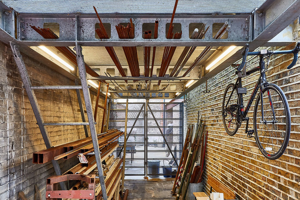 The underside of the extension, at ground floor, was designed as an occasional working bay and storage for the workshop. The steel structure was adapted to create a personalised shelving system