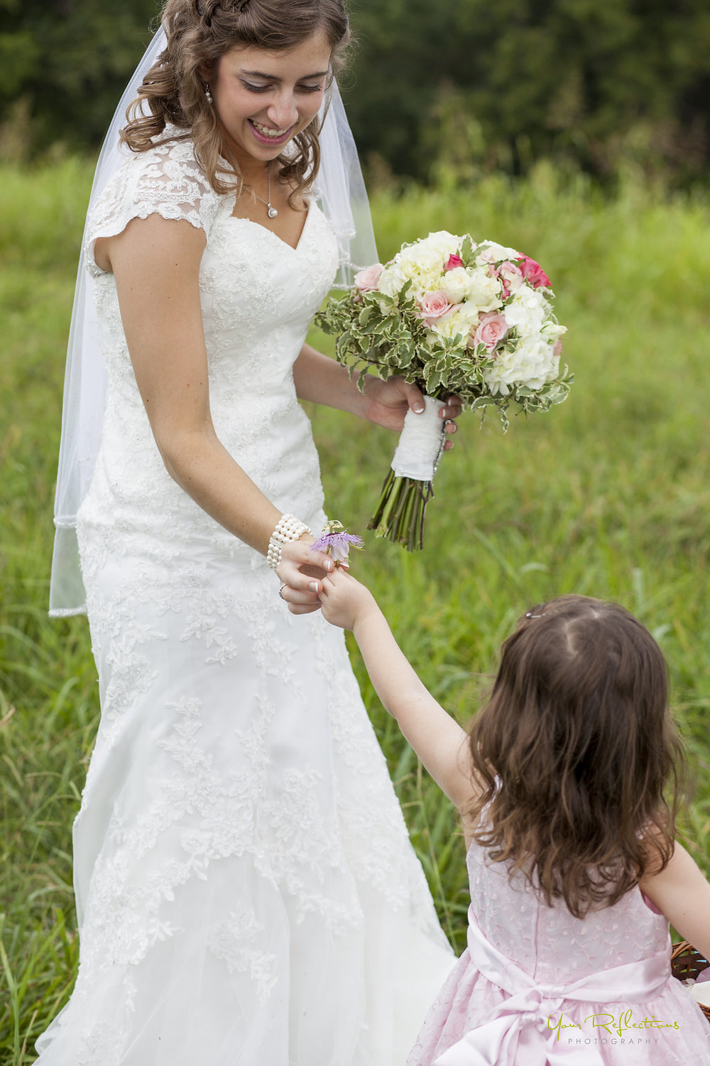 flower girl hands the bride a wildflower.jpg