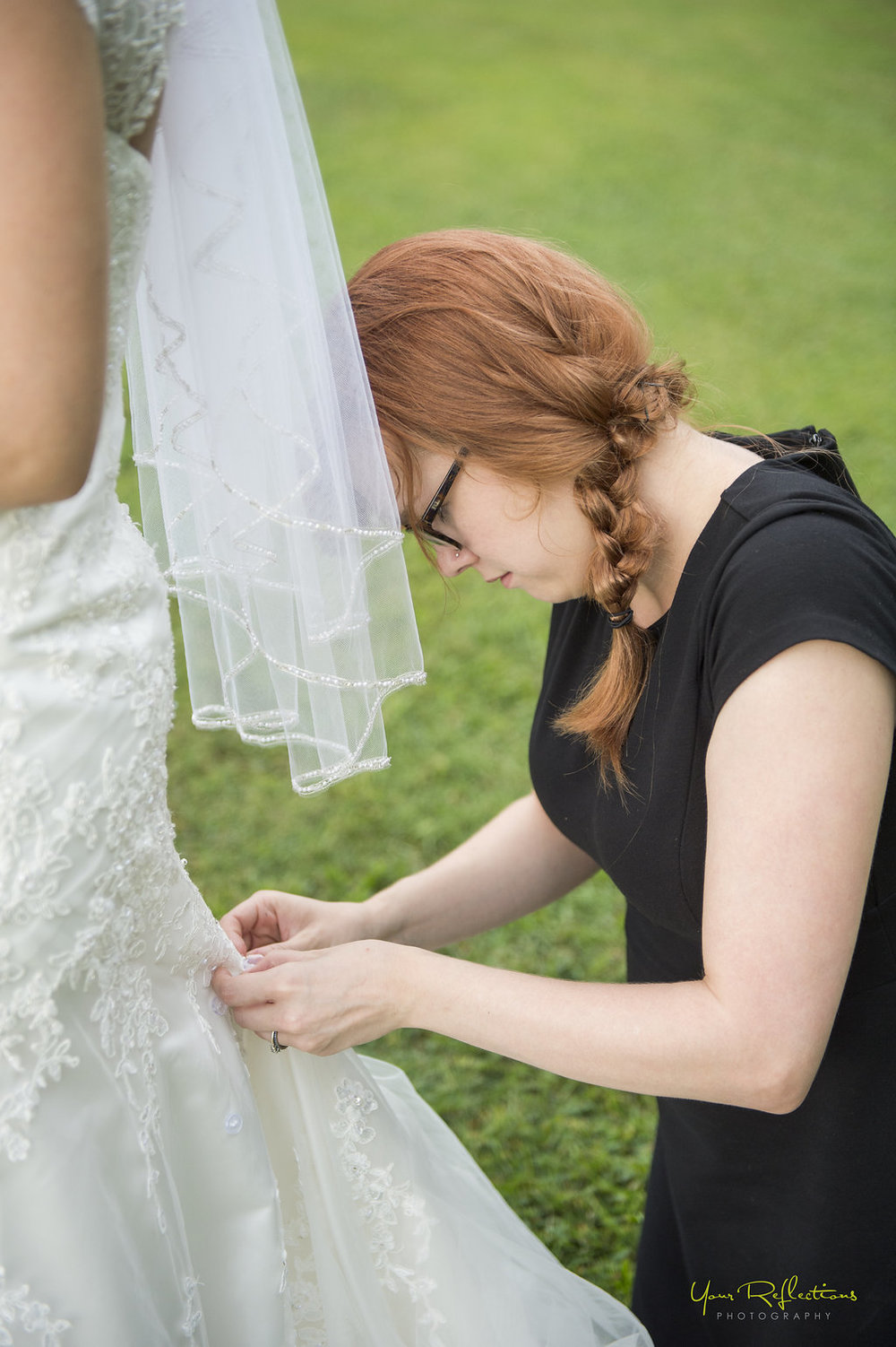 wedding coordinator fixes bride's train.jpg