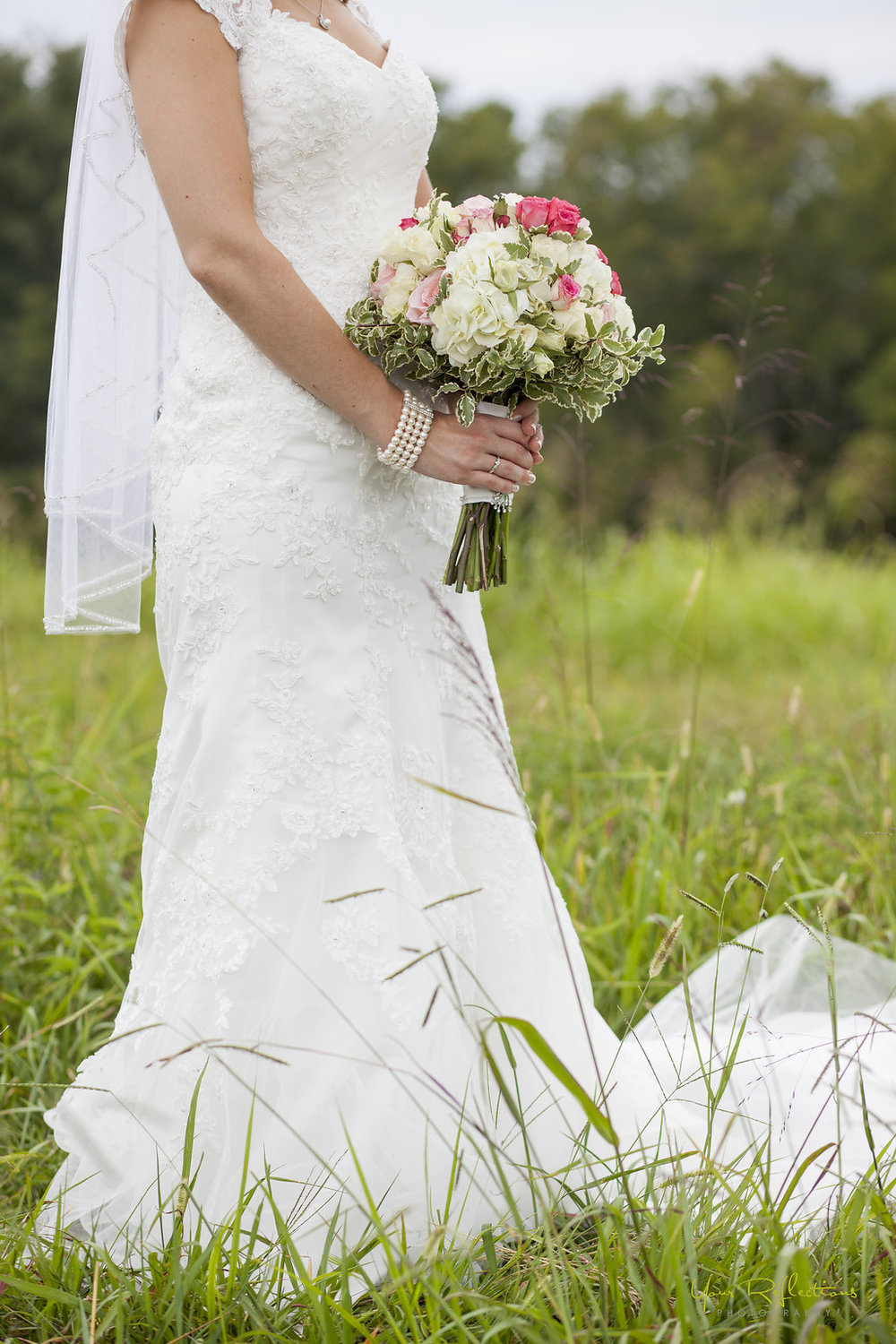 bride holding her rose and hydrangia bouquet.jpg