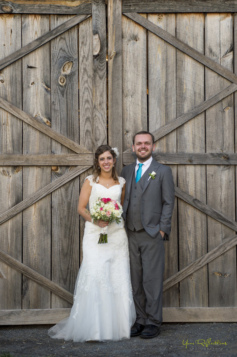 bride and groom in front of barn doors.jpg