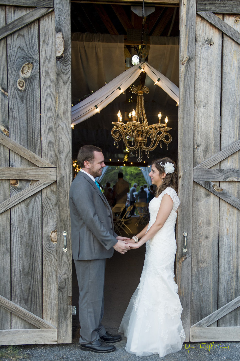 bride and groom stand in barn doorway.jpg
