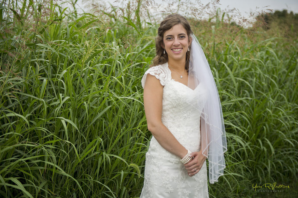 bride standing by tall field of grass.jpg