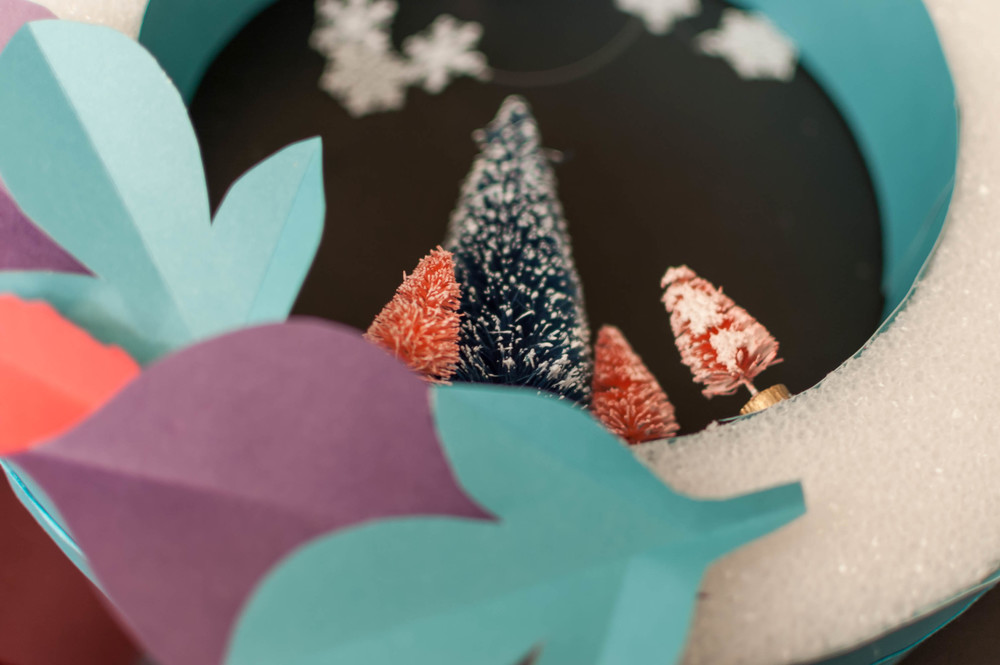 A bright, colorful Christmas wreath DIY! Use this tutorial to make a fun, unique and whimsical paper wreath to hang on your front door this holiday season! @paperswalloweve