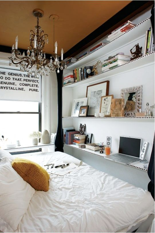 -via brightnest.com / The shelving doubles as a desk and reaches all the way up to the ceiling for ample storage.  They managed to squeeze in a nice big bed and a statement chandelier.  Not bad!