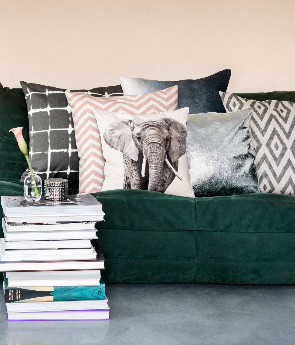 -via H&M home / The green sofa brings in the major color, while the muted tones, the silver metallic and the printed elephant add major interest. I'd love to chill on that set-up!