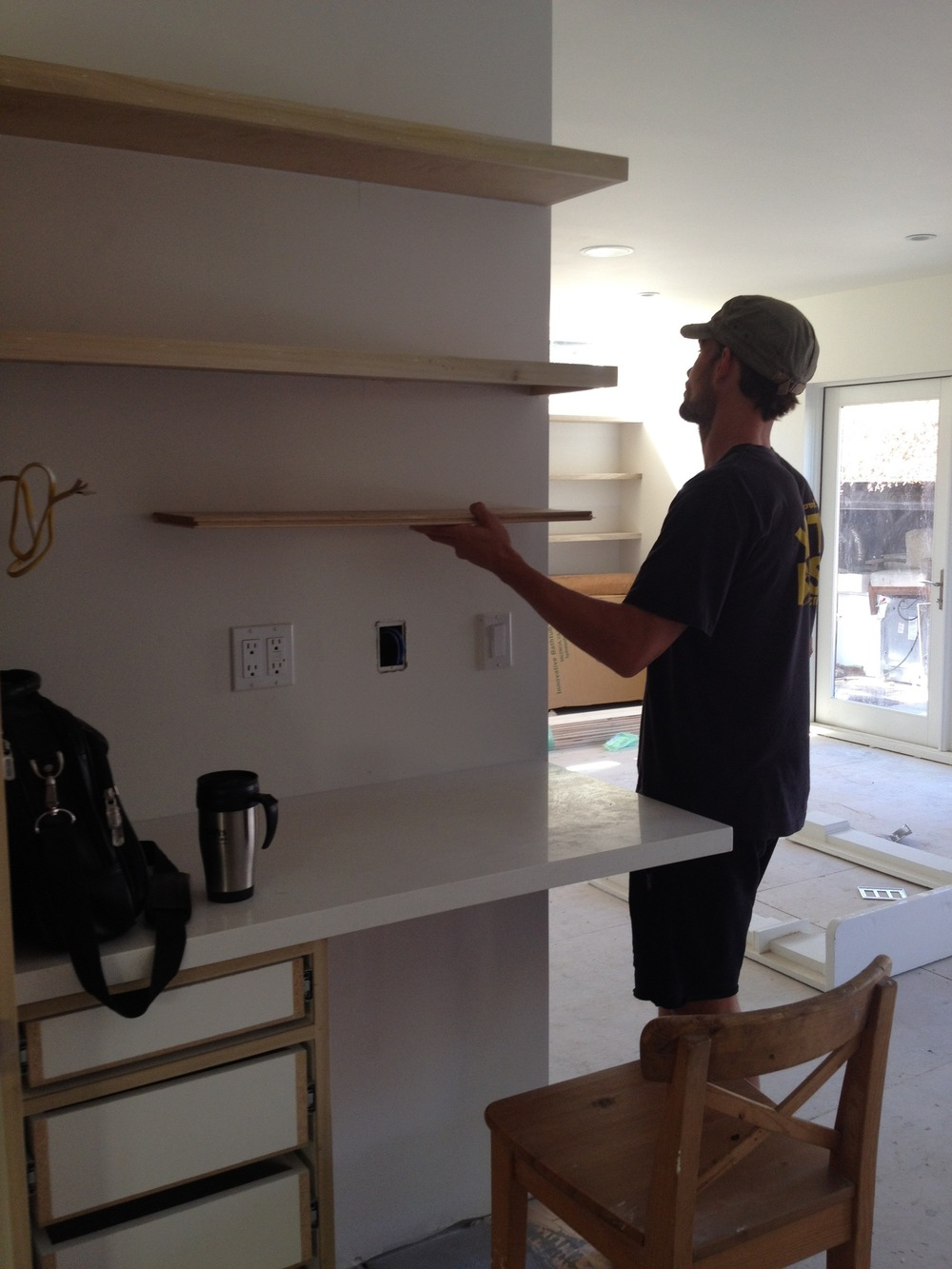 This is a progress photo of Joel holding up a potential third floating shelf in the desk area of the kitchen.  We may have had him do that a few too many times. :)