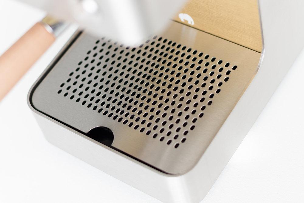 Das Abtropfgitter, auf dem die Tassen abgestellt werden, ist mit einem Lochmuster versehen, welches sich zur Mitte hin verdichtet. Die Auffangschale aus dunklem Kunststoff verschwindet optisch unter dem Gitter.