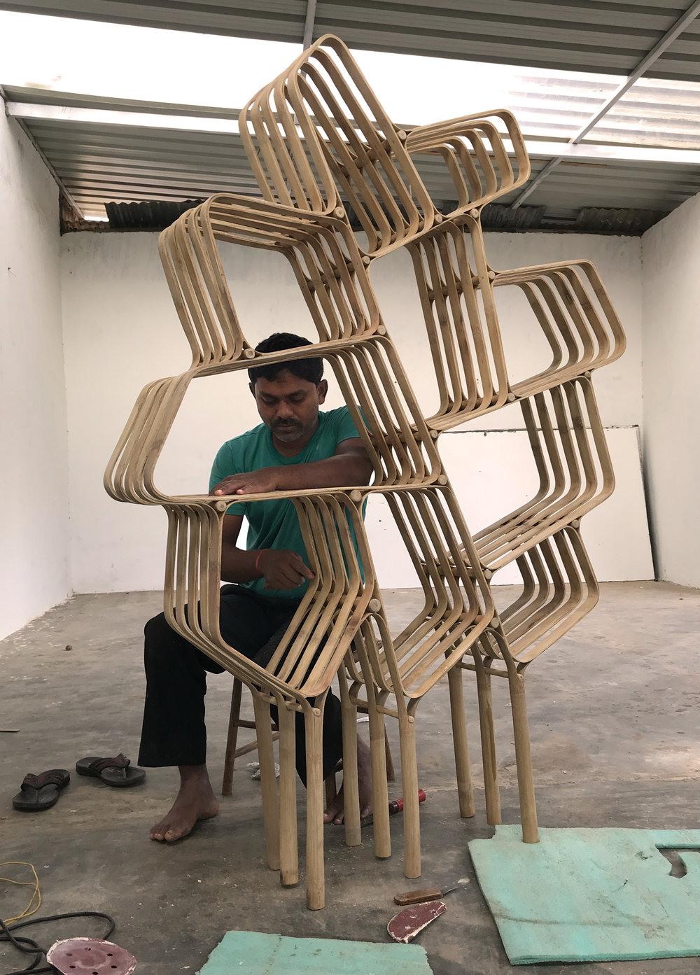 "An artisan is finishing the bamboo book shelf ""tree""."