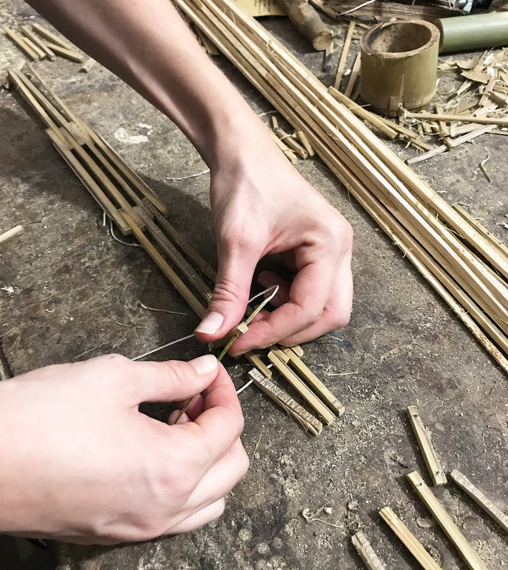 Building a structure with bamboo sticks.