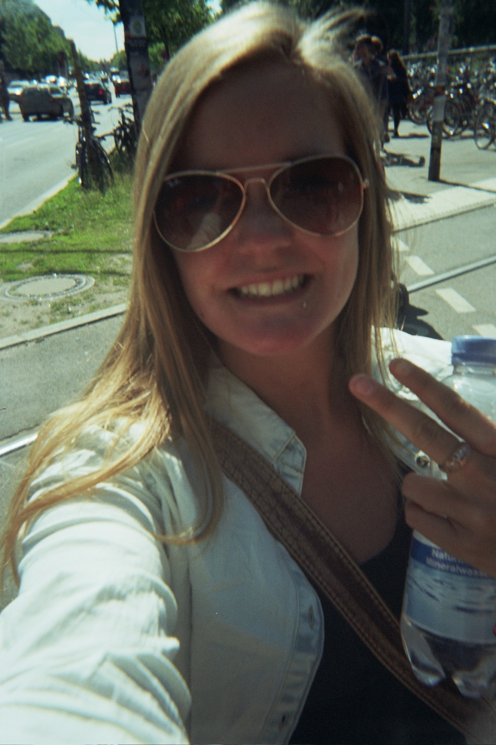 That's me. Clara. With a bottle of vodka disguised as the elixir of life. Yes I know, it's a selfie right in the middle of the road. But fuck it, life is cheap. And it's 30° out here. So why not?