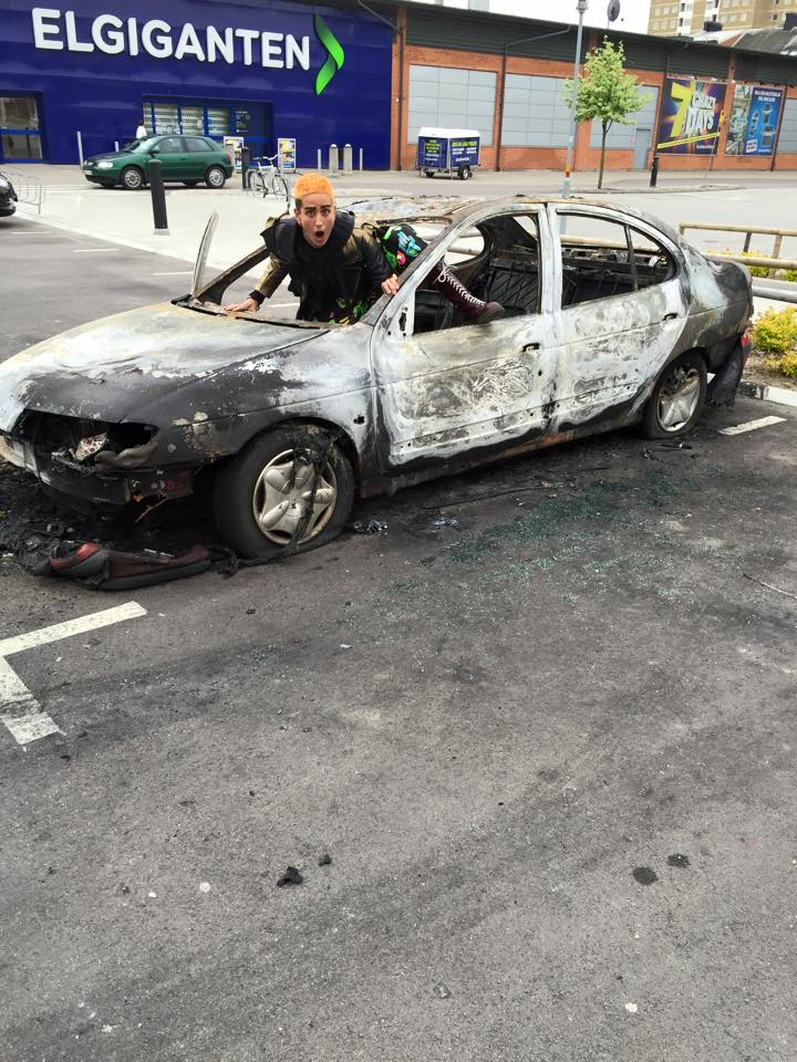 An immigrant lesbian, Vladica Culic, posing with a burnt car in Malmö, Södervärn.