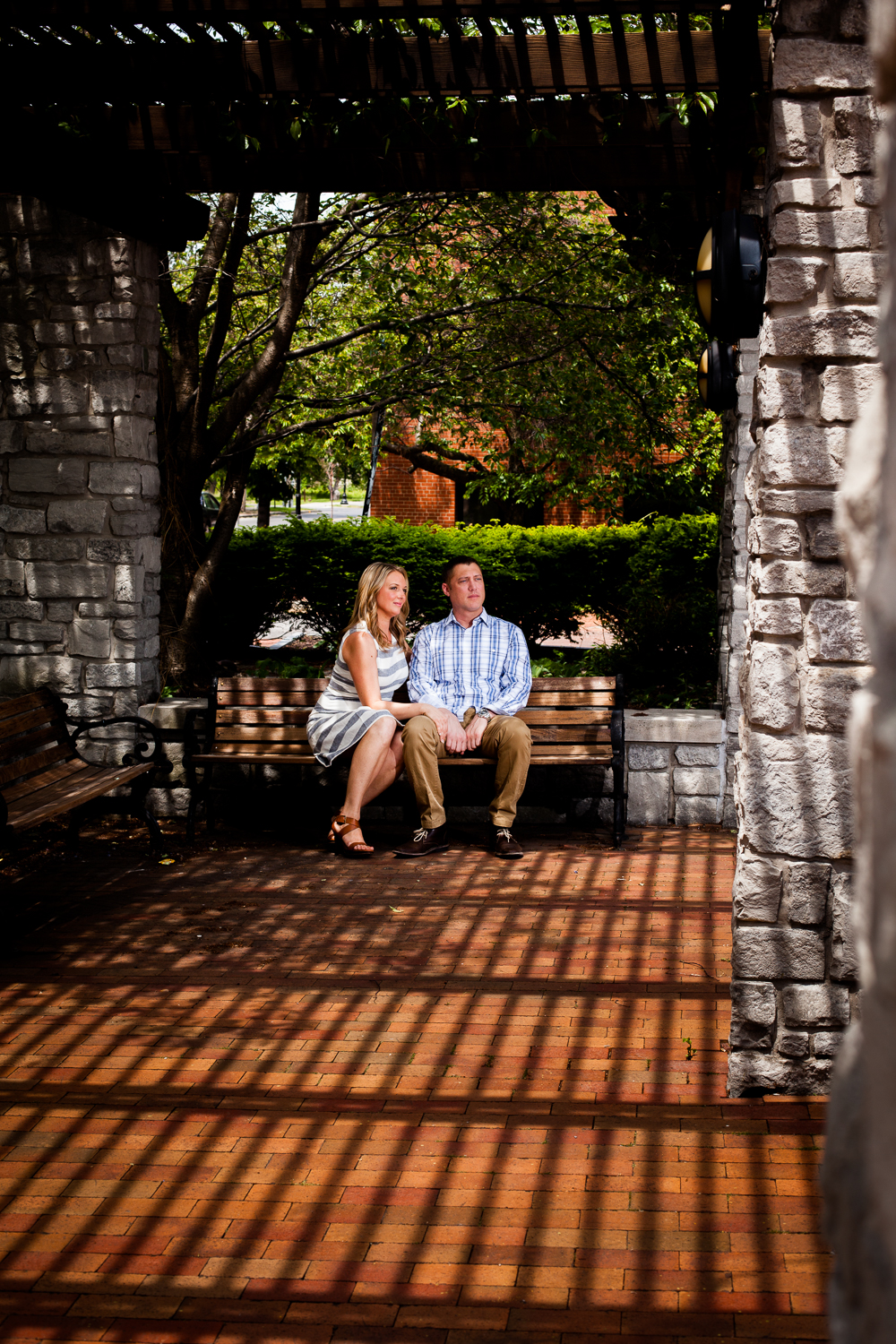 Bride and groom in shadows sitting on park bench.