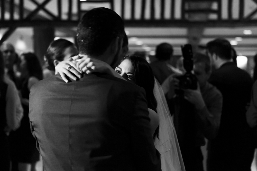 black and white photo bride looks at groom during first dance