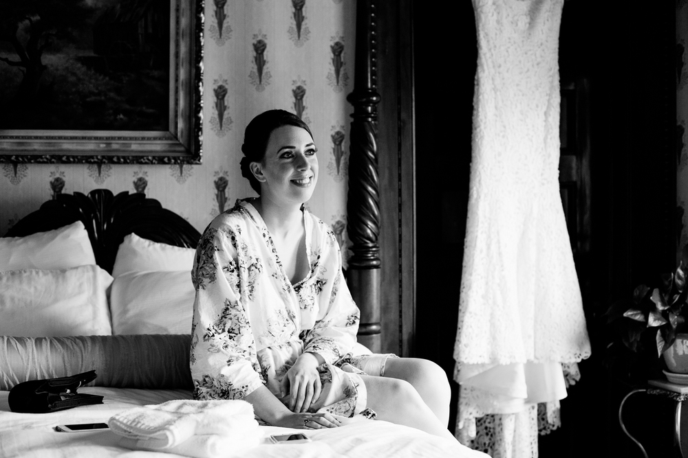 A bride smiles with her wedding dress.