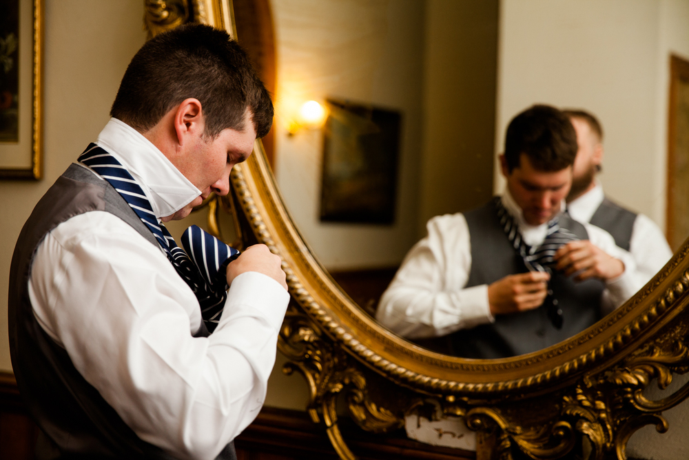 Groom puts on his tie for a Syracuse Wedding