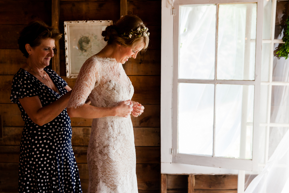 A mother helps the bride with her dress
