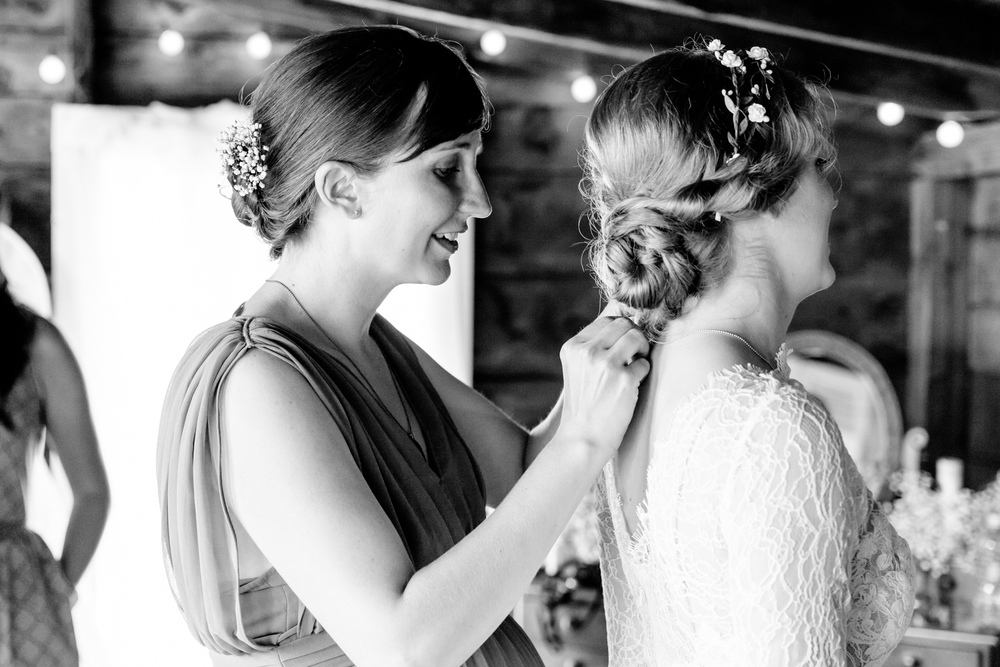 A sister helps the bride get ready.