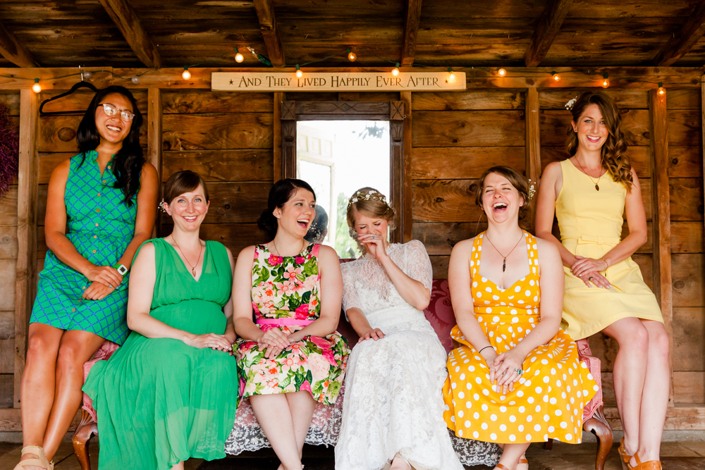 bridesmaids and bride sit on couch laughing in the Adirondacks