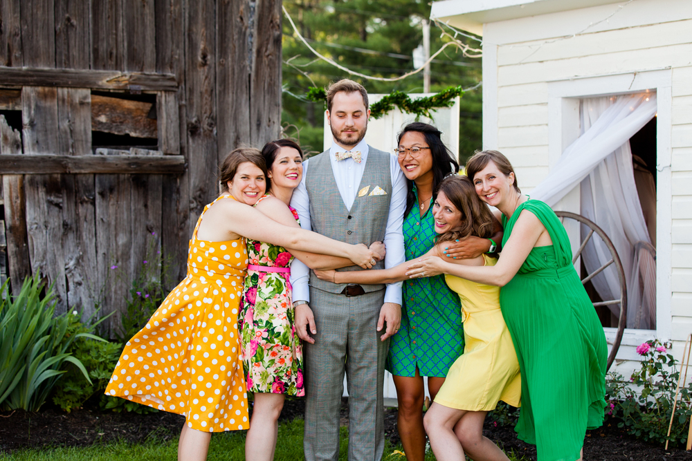 Groom stands with bridesmaids