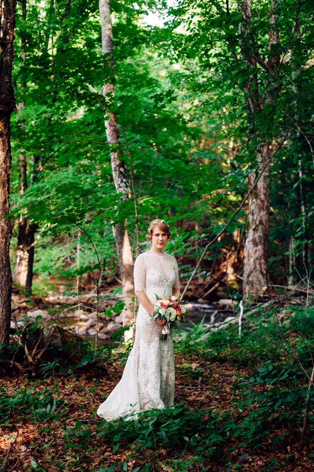 A bride stands in the Adirondack woods