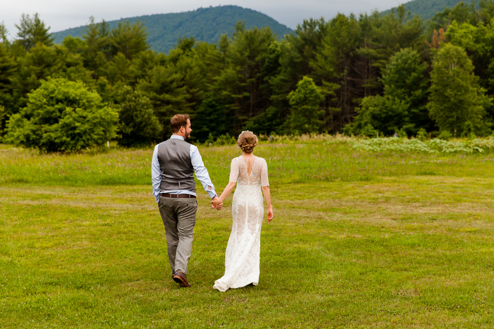 Bride and groom walk into a field