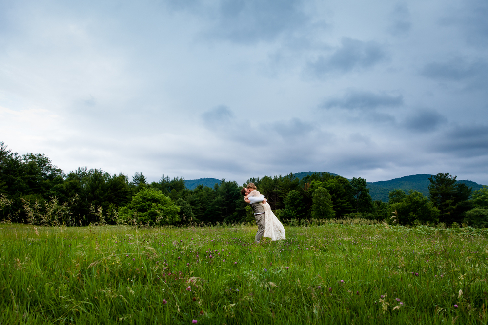 Groom lifts bride in a field in Upstate New York