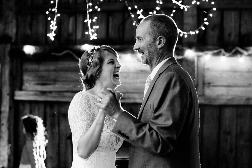 Bride and father share a dance in a barn