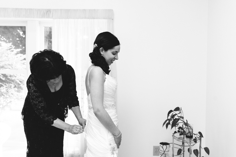 Syracuse Wedding Photographer Captures Mother and Bride Putting on Dress