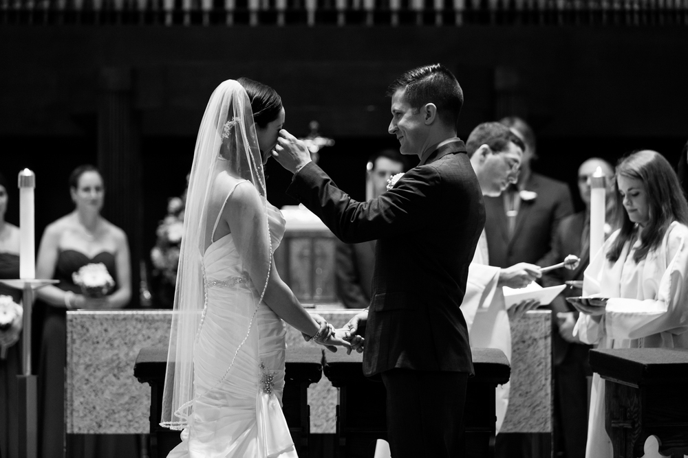A groom wipes away a tear during the wedding ceremony