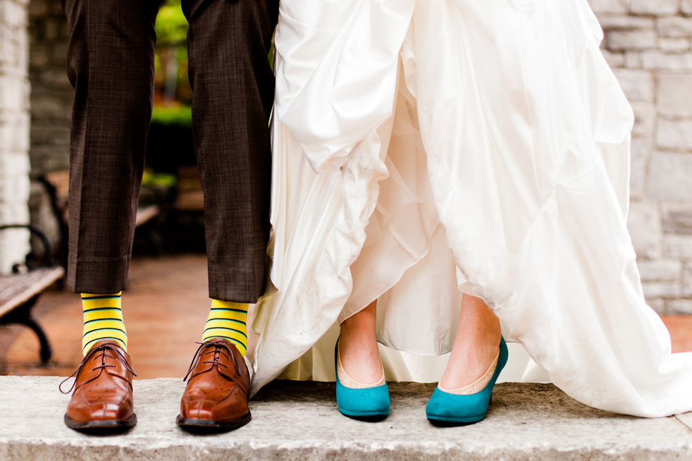 Bride and groom show off wedding shoes