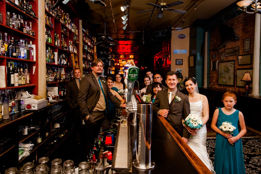 Bridal party stands around a bar