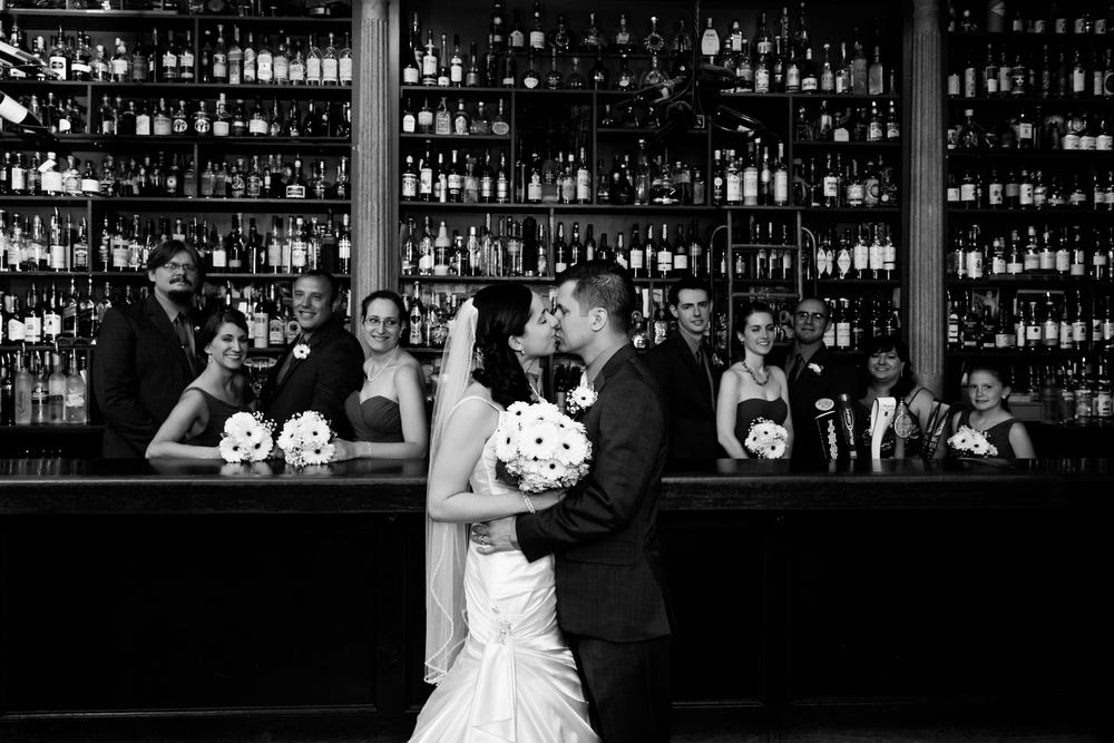 Bride and groom kiss in front of the bar at Al's Wine and Whiskey Lounge in downtown Syracuse, NY