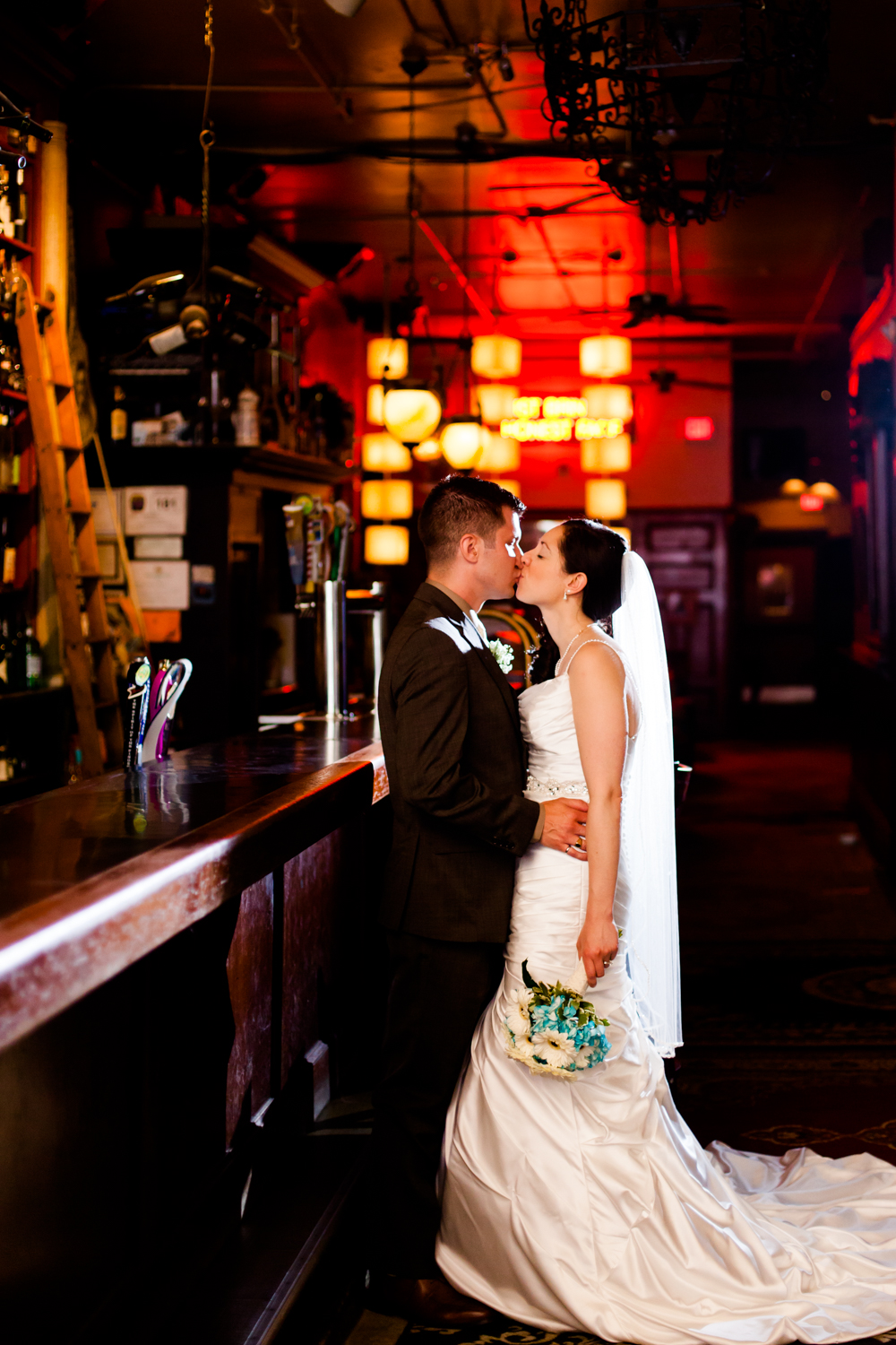 Bride and groom share a kiss at Al's Wine and Whiskey Lounge