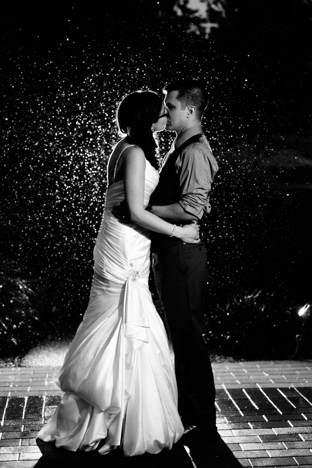 Bride and groom kiss in the rain