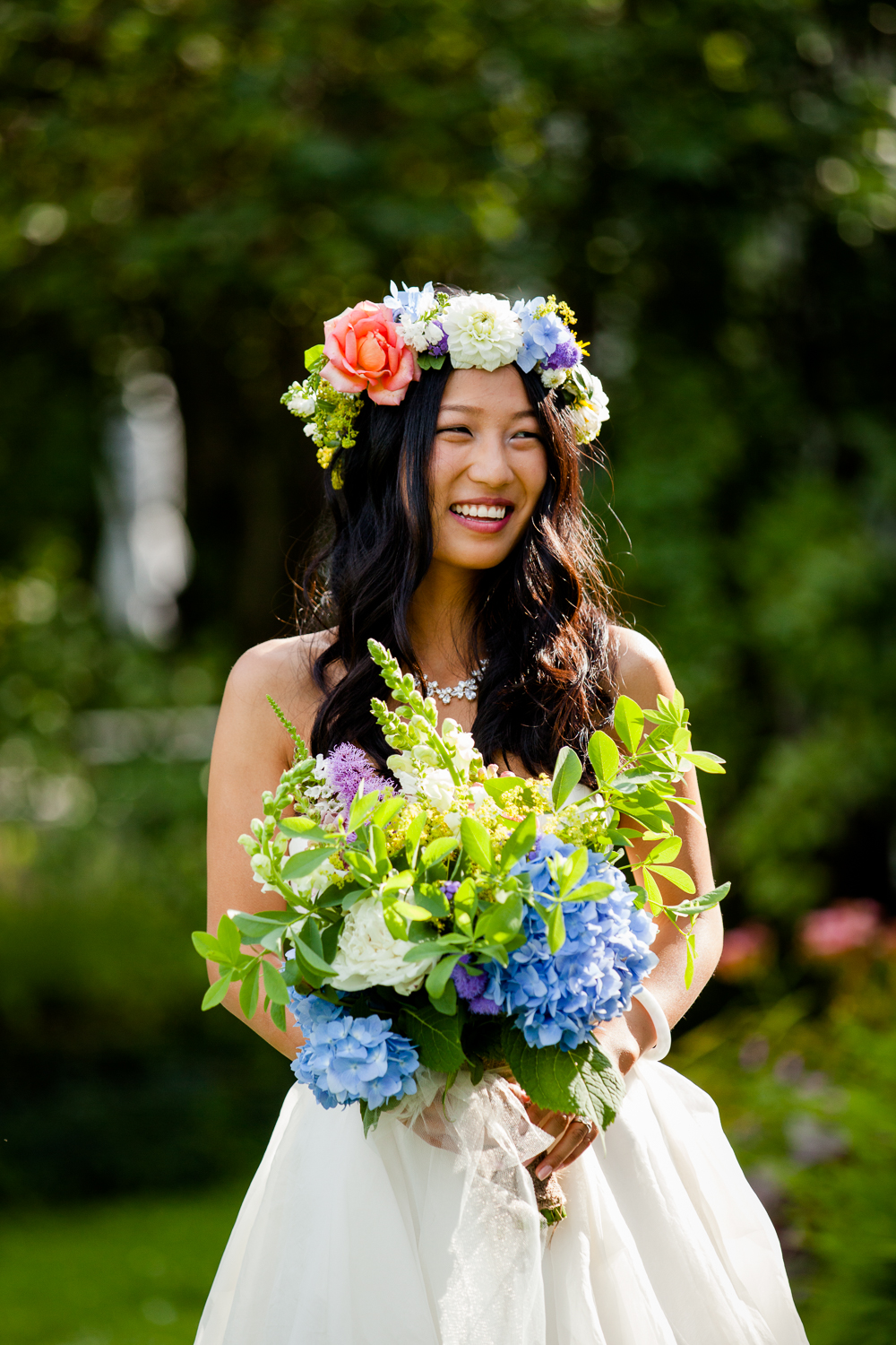 Bride smiles while holding bouquet.