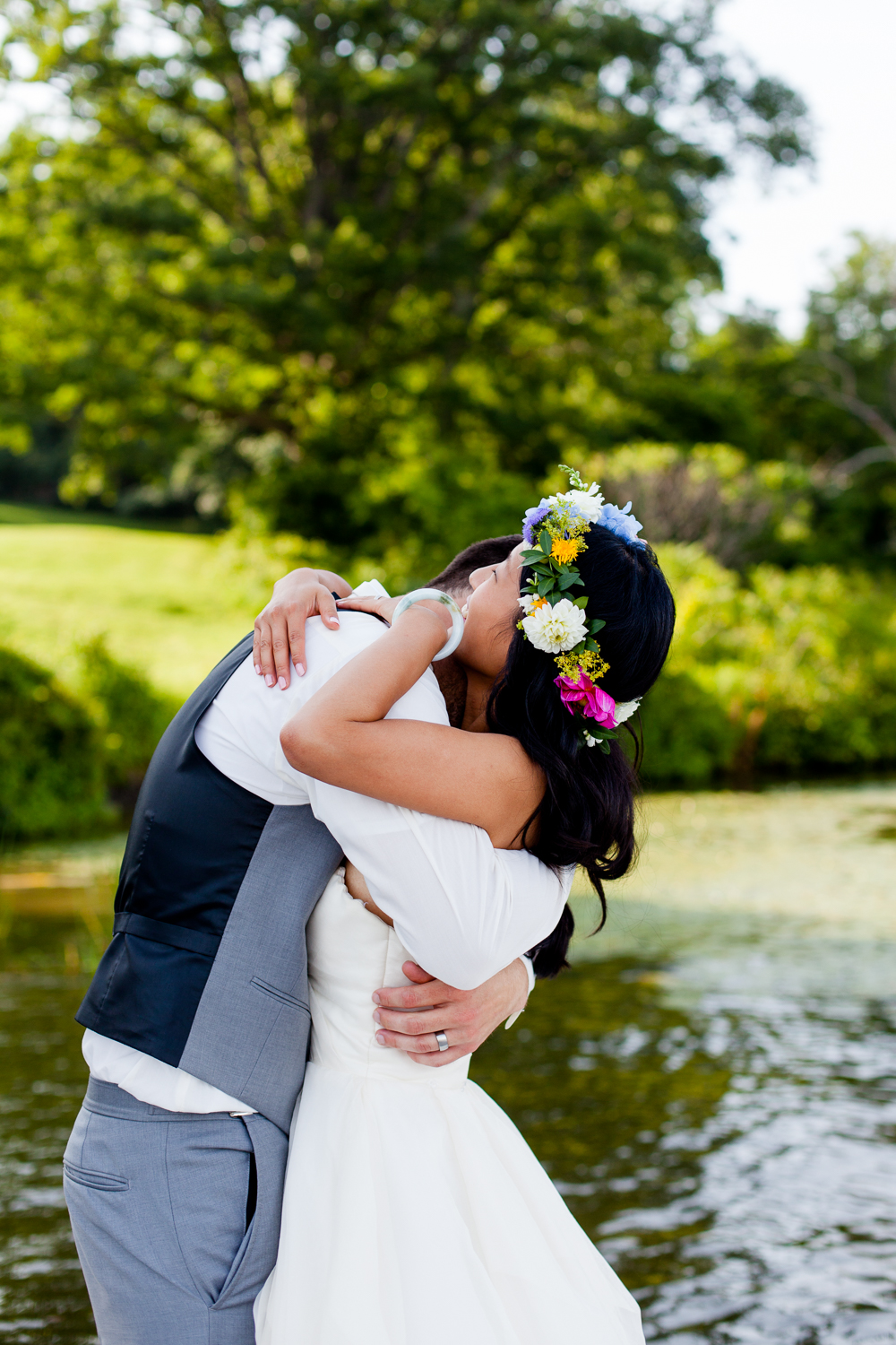 bride and groom hug on the dock